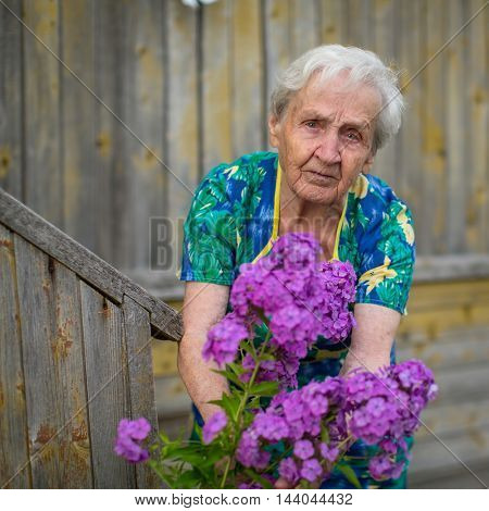 An elderly woman caring for flowers outdoors.