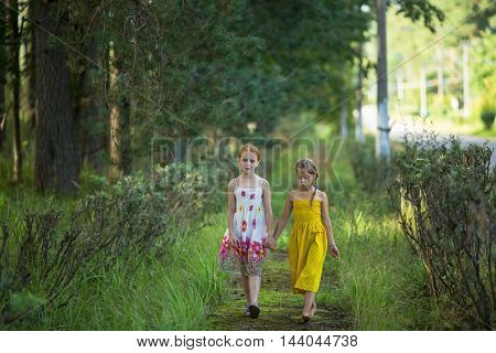 Two little girl go for handle the avenue in the Park.