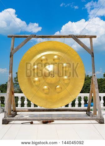 Golden large gong in thai temple with blue sky and cloud background.