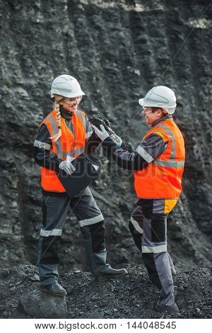 Two specialists examining coal at an open pit