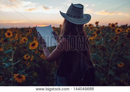 Girl in a cowboy hat in a sunflower field with a map looking for the path. Sunset