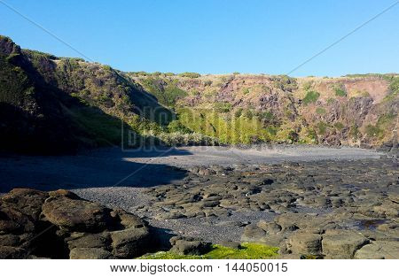 clear sky cliffs rock formation sea grass