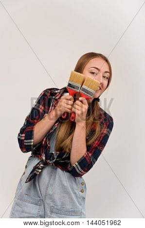 woman holding two paint brushes. tools for repair and painting