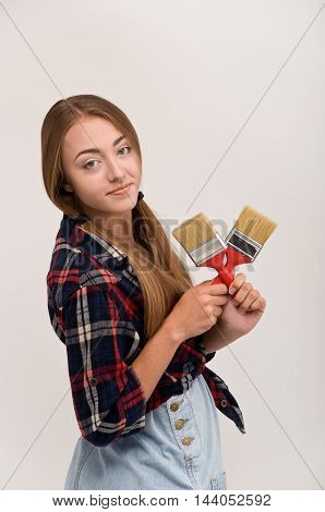 woman holding paint brushes. tools for repair and painting