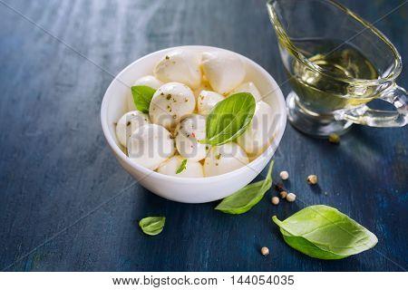 Small Mozzarella balls, fresh basil and olive oil. Selective focus