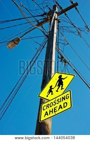 Children Crossing Ahead sign on electric pole with wire against clear sky