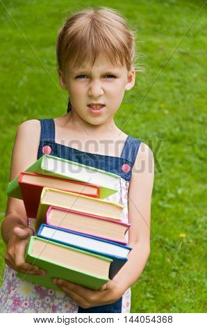 little schoolgirl holding a book in her hands and it is heavy