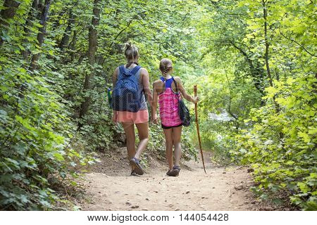 Family hiking together in the woods. Mother and daughter holding hands as they walk together