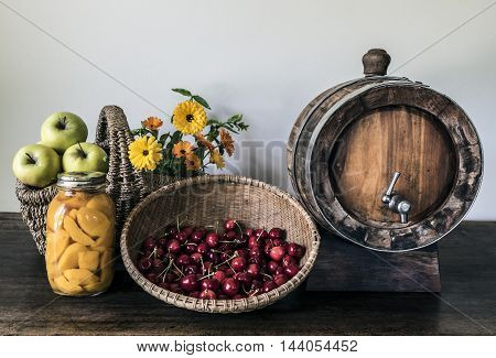Apples, cherries in a basket, peaches in syrup and a small barrel