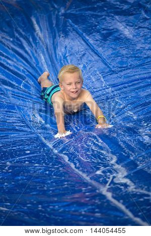 Smiling boy playing on a slip and slide outdoors