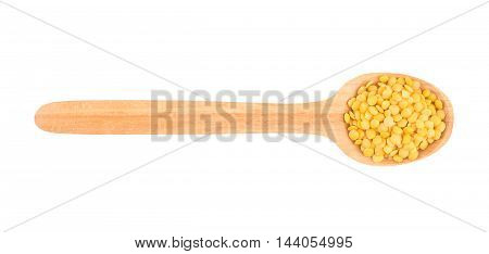 Yellow lentil in a wooden spoon. Top view.