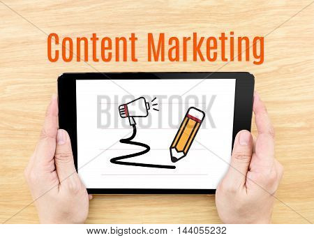 Hand Holding Tablet With Content Marketing Word On Wooden Table,digital Business Concept