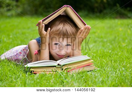 Little schoolgirl reading a book. smart little pupil