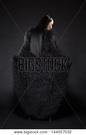 Beautiful watch lady in black clothes showing her back over dark background. Young magic lady with long black hair.