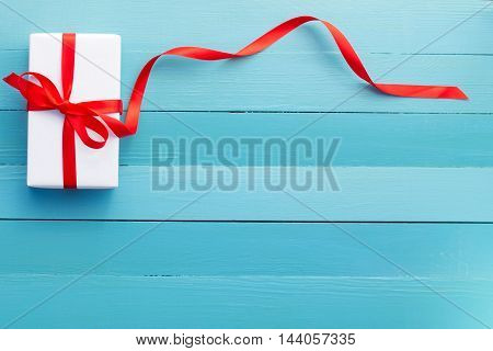 gift in white packing and a red ribbon
