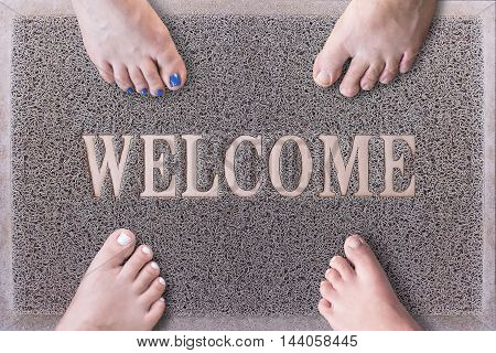 Welcome Door Mat With Funny Family Feet. Friendly Grey Door Mat Closeup with Four Bare Feet Standing. Welcome Carpet. Four Feet on Foot Scraper.