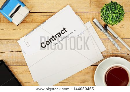 envelope with contract on wooden desk top view