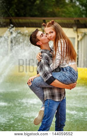 Enamoured teenagers embrace. Girlfriend and boyfriend strolling in a city park. A boy holding the girl in his arms. First love. He falls in love. Date.