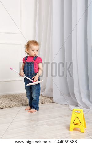 Girl checks cleaning cleanliness in the room. Small mother's helper. Household chores. Girl holds in the hands of the mop.