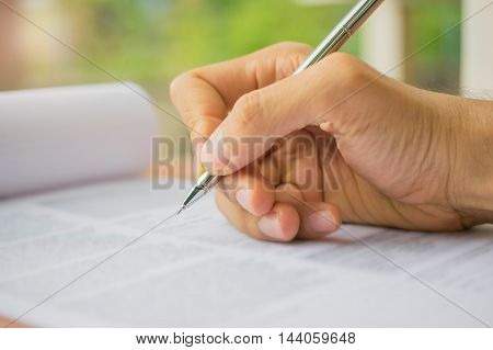 Hand with pen over application form, job application