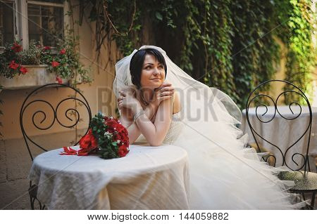 Thinking bride sitting on table outdoor at wedding