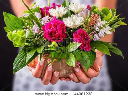 closeup of female hands holding gift and beautiful vintage wedding bouquet of rose white gerberas and greenery on black background