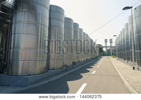 Stainless steel fermenters used to make wine toned image.