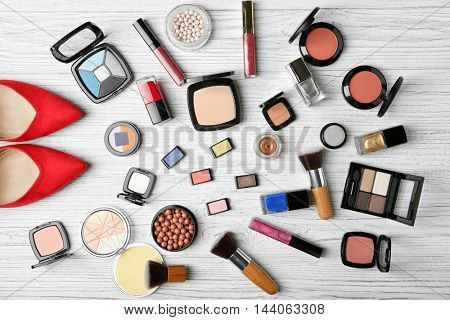 Makeup products, brushes and female shoes on wooden background