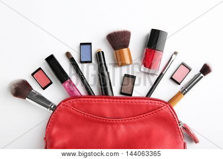 Makeup bag with cosmetic products and brushes on white background