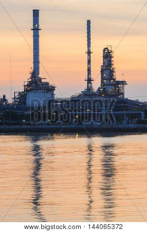 Petrochemical plant at sunrise with reflection on water