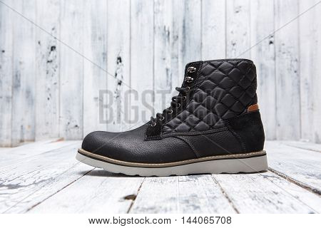 Footwear concept. Winter black men's shoe represented on white wooden background. One boot with white sole.