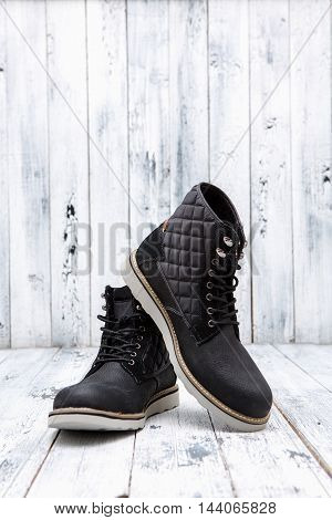 Footwear concept. Men's winter leather boots of black color are nice idea for active holidays isolated on white wooden background.