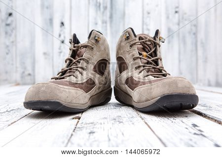 Footwear concept. Men's winter boots represented one near another over wooden background. Leather footwear are used for winter weather.