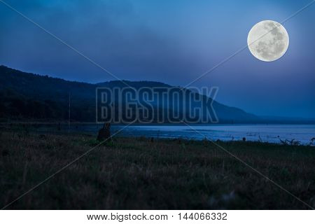 Mountain and river against blue sky and beautiful full moon at night. Beauty of nature use as background. Outdoors. The moon were NOT furnished by NASA.