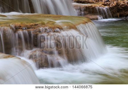 Water flowing over rocks in waterfall cascade in a forest