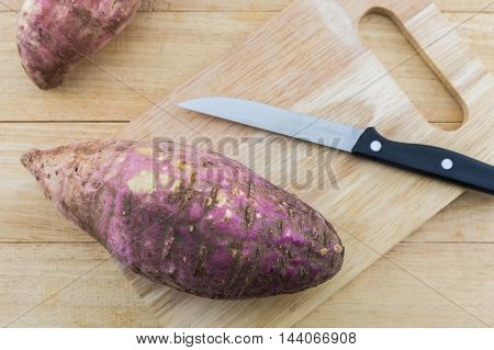 Sweet potato on wooden cutting board on the wood background.