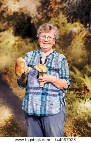 Smiling Elderly Woman - Mushroom Picker In Autumn With Two Ceps