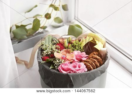 Gift box with flowers and cookies on windowsill closeup