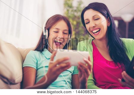 Mother and daughter laughing on couch at home in the living room