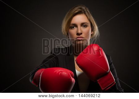 Serious businesswoman posing in red-coloured boxing gloves isolated on dark. Real leader in black business suit looking at the camera.