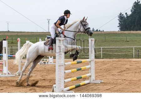 SVEBOHOV CZECH REPUBLIC - AUG 20: Longhaired beautiful horsewoman on a white horse is jumping at