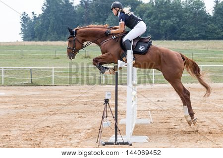 SVEBOHOV CZECH REPUBLIC - AUG 20: Side view of beautiful longhaired blond horsewoman jumping a brown horse at