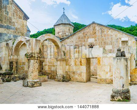 The view from gavit (frontage hall) of St Astvatsatsin Church on the stone wall and dome of St Grigor Church Haghartsin Monastery Armenia.