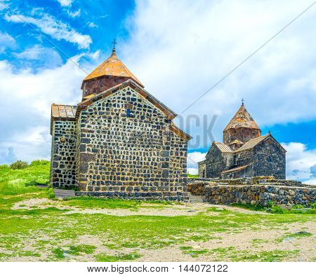 The black stone Churches of Holy Apostles and Holy Mother of God on the green meadow on the top of the hill of Sevan Peninsula Armenia.