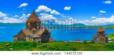 Panoramic view of Sevan Peninsula with both Churches of Sevanavank Monastery - Holy Apostles and Holy Mother of God on the green meadow and with the pure Sevan Lake on the background Armenia.
