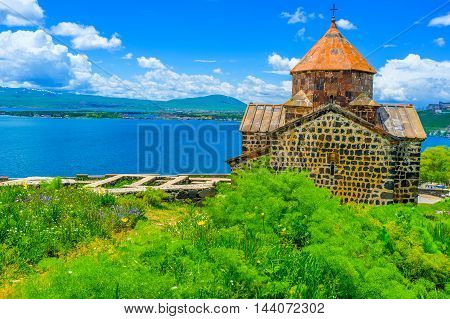 The Sevanavank Monastery surrounded by lush greenery of Sevan Peninsula Armenia.