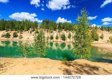Quarry Or Lake Or Pond With Sandy Beach, Green Water, Trees And Hills With Cloudly Sky