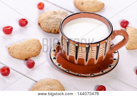 cup of milk with oatmeal cookies and cherry on a white background
