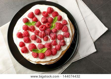 Tasty raspberry cake on napkin, top view