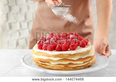 Woman powdering berry cake